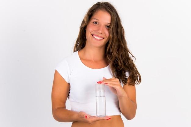 Giovane donna con acqua micellare in bottiglia Foto Premium