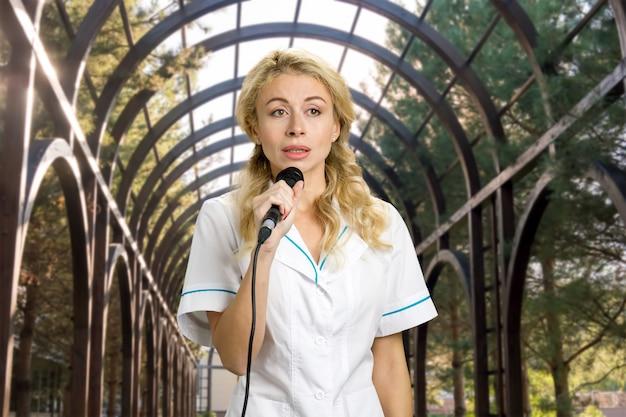 Microfono della holding della giovane donna. bella ragazza in uniforme bianca che dà un discorso sulla conferenza all'aperto.