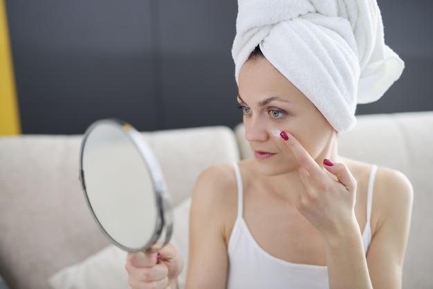 Giovane donna che tiene lo specchio nelle mani e applicare la crema sul viso in bagno. cura quotidiana della pelle
