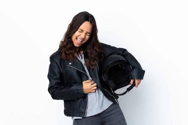 Giovane donna che tiene un casco da motociclista su sfondo bianco isolato che fa il gesto della chitarra