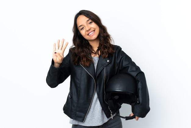 Giovane donna in possesso di un casco da motociclista su bianco isolato felice e contando quattro con le dita