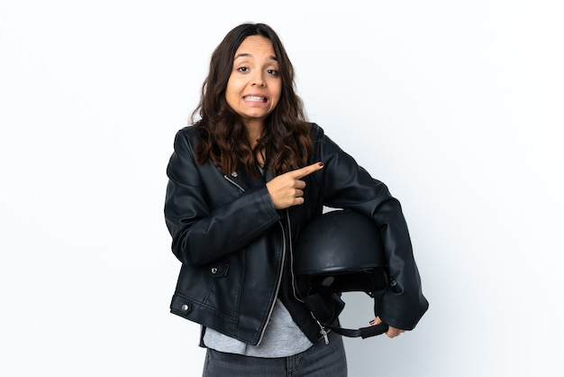 La giovane donna che tiene un casco del motociclo sopra la parete bianca isolata ha spaventato e che indica al lato