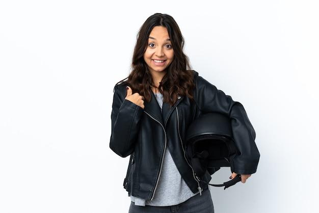 Giovane donna che tiene un casco del motociclo sopra la parete bianca isolata con l'espressione facciale di sorpresa