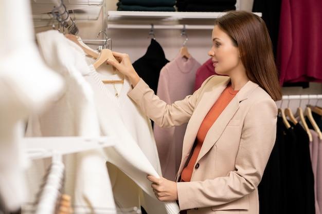 Giovane donna che tiene in mano un nuovo maglione e lo sceglie per se stessa nel negozio di abbigliamento