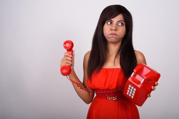 Giovane donna che tiene il vecchio telefono mentre pensa e sembra infastidito