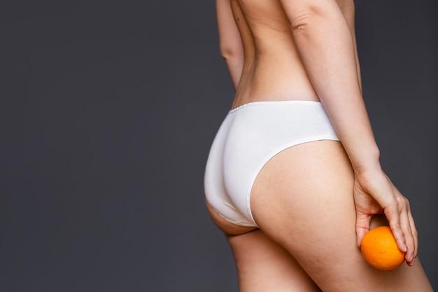 Giovane donna che tiene un'arancia su una parete leggera. concetto di problema della cellulite