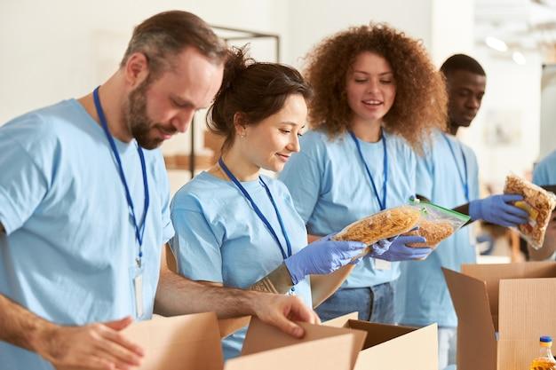 Giovane donna che tiene in mano un pacco di volontari di pasta in guanti protettivi che smistano il cibo in imballaggio