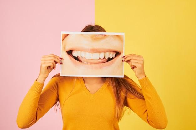Giovane donna che tiene una foto di una bocca sorridente