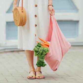 Giovane donna che tiene il sacchetto della spesa in cotone rosa con verdure. borsa ecologica riutilizzabile per lo shopping. rifiuti zero concetto.
