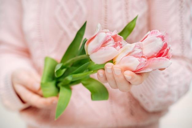 Giovane donna che tiene i tulipani rosa su sfondo bianco. sfocatura ritratto, primo piano, copia spazio, messa a fuoco selettiva.