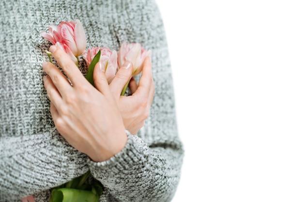 Giovane donna che tiene i tulipani rosa su sfondo bianco. sfocatura ritratto, primo piano, copia dello spazio.