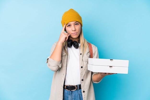 Giovane donna che tiene pizze isolato tempio puntato con il dito, pensando, concentrato su un compito