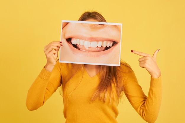 Giovane donna che tiene il dito puntato alla foto della bocca sorridente che mostra i suoi denti su sfondo giallo. concetto di dentista