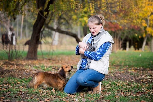 Giovane donna che tiene il coniglio e gioca con il cane all'aperto
