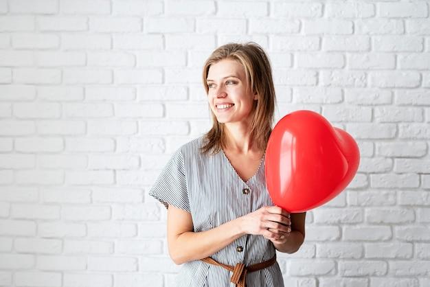 Giovane donna che tiene leggere il palloncino a forma di cuore sul fondo del muro di mattoni bianchi con lo spazio della copia