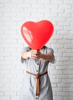 Giovane donna che tiene leggere il palloncino a forma di cuore su sfondo bianco muro di mattoni