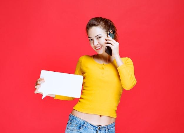 Giovane donna che tiene in mano una scheda informativa rettangolare e parla con uno smartphone nero