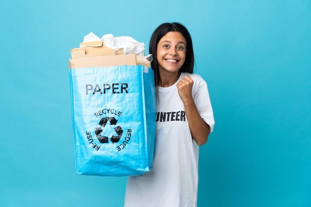Giovane donna che tiene un sacchetto di riciclaggio pieno di carta che celebra una vittoria nella posizione del vincitore