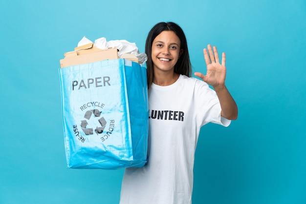 Giovane donna che tiene un sacchetto di riciclaggio pieno di carta che conta cinque con le dita