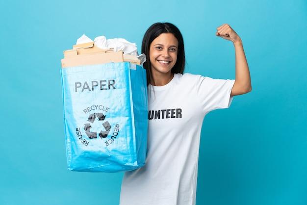 Giovane donna che tiene un sacchetto di riciclaggio pieno di carta facendo un gesto forte
