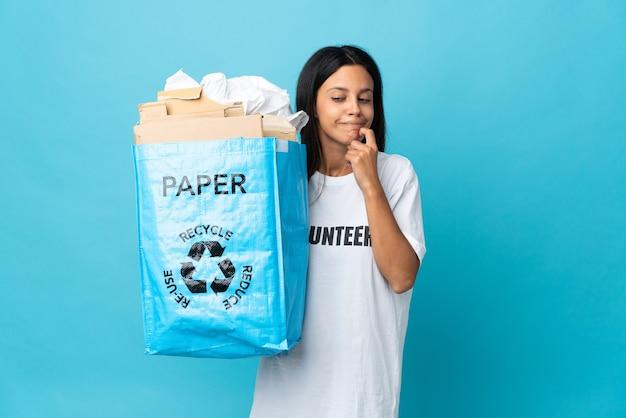 Giovane donna che tiene un sacchetto di riciclaggio pieno di carta che ha dubbi e che pensa