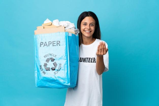 Giovane donna che tiene un sacchetto di riciclaggio pieno di carta che invita a venire con la mano