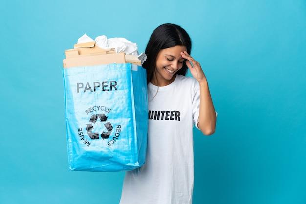 Giovane donna che tiene un sacchetto di riciclaggio pieno di risata di carta