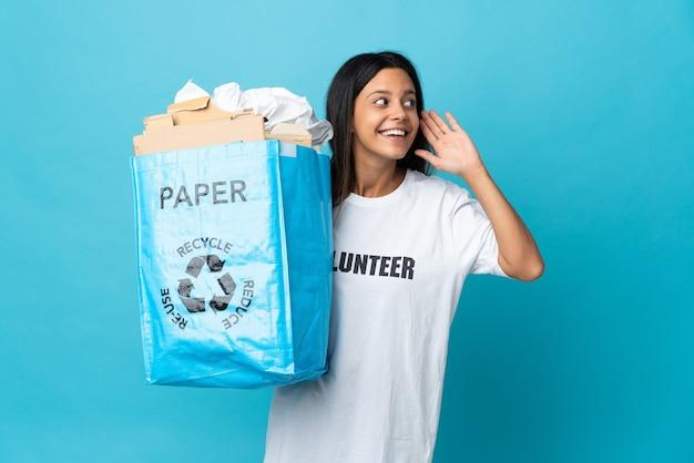 Giovane donna che tiene un sacchetto di riciclaggio pieno di carta ascoltando qualcosa mettendo la mano sull'orecchio