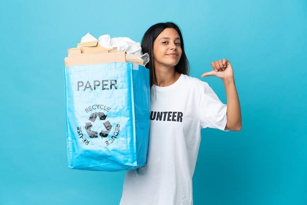 Giovane donna che tiene un sacchetto di riciclaggio pieno di carta orgoglioso e soddisfatto di sé