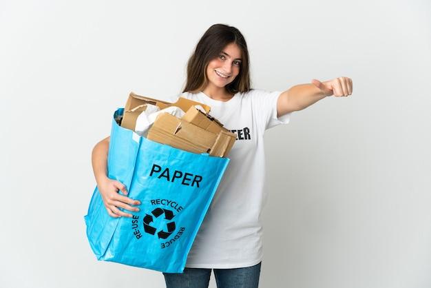 Giovane donna che tiene un sacchetto di riciclaggio pieno di carta da riciclare isolato su bianco dando un pollice in alto gesto