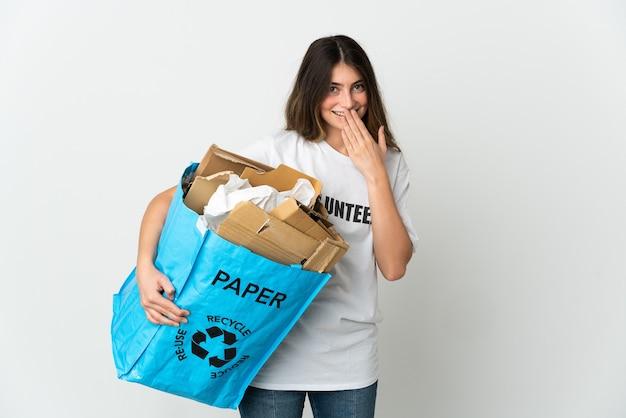 Giovane donna in possesso di un sacchetto di riciclaggio pieno di carta da riciclare isolata on white felice e sorridente che copre la bocca con la mano