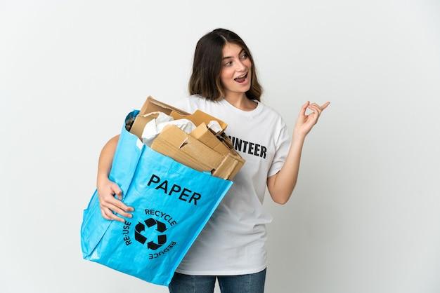 Giovane donna che tiene un sacchetto di riciclaggio pieno di carta da riciclare isolato su bianco che intende realizzare la soluzione mentre si alza un dito