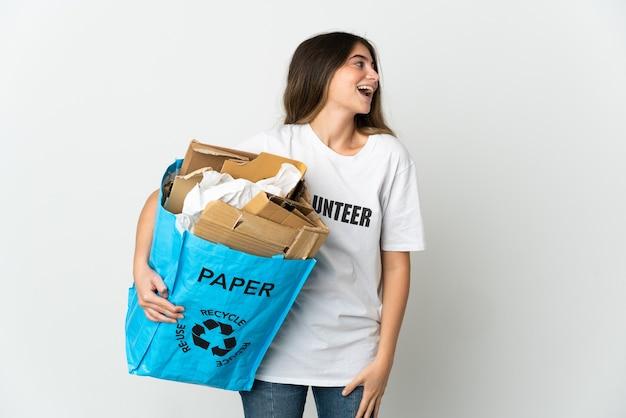 Giovane donna in possesso di un sacchetto di riciclaggio pieno di carta da riciclare isolato su bianco ridendo in posizione laterale