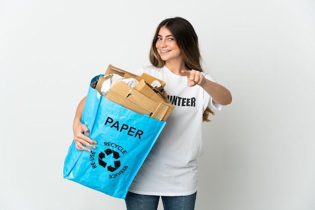 Giovane donna che tiene un sacchetto di riciclaggio pieno di carta da riciclare isolato sulla parte anteriore puntata bianca con l'espressione felice
