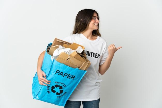 Giovane donna che tiene un sacchetto di riciclaggio pieno di carta da riciclare isolato su bianco che punta al lato per presentare un prodotto