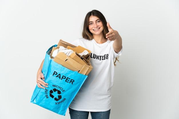 Giovane donna in possesso di un sacchetto di riciclaggio pieno di carta da riciclare isolato su bianco si stringono la mano per chiudere un buon affare
