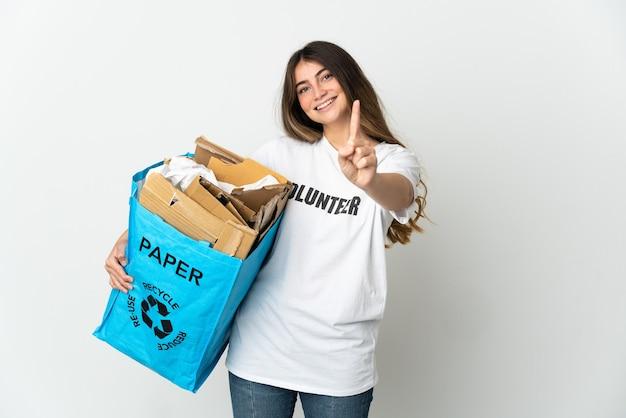 Giovane donna che tiene un sacchetto di riciclaggio pieno di carta da riciclare isolato su bianco che mostra e che alza un dito