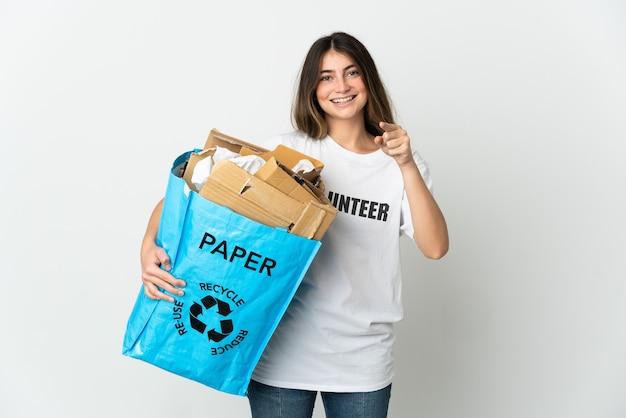 Giovane donna che tiene un sacchetto di riciclaggio pieno di carta da riciclare isolato su bianco sorpreso e rivolto verso la parte anteriore