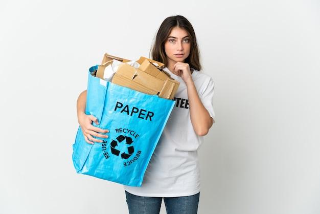 Giovane donna che tiene un sacchetto di riciclaggio pieno di carta da riciclare isolato sul pensiero bianco