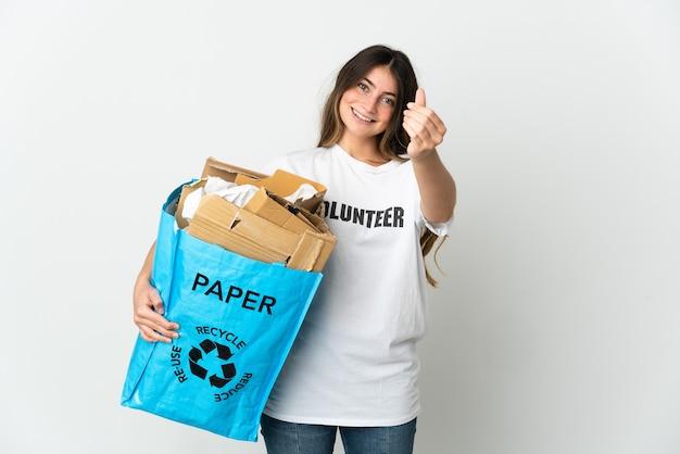 Giovane donna che tiene un sacchetto di riciclaggio pieno di carta da riciclare isolato sul muro bianco che fa gesto di denaro