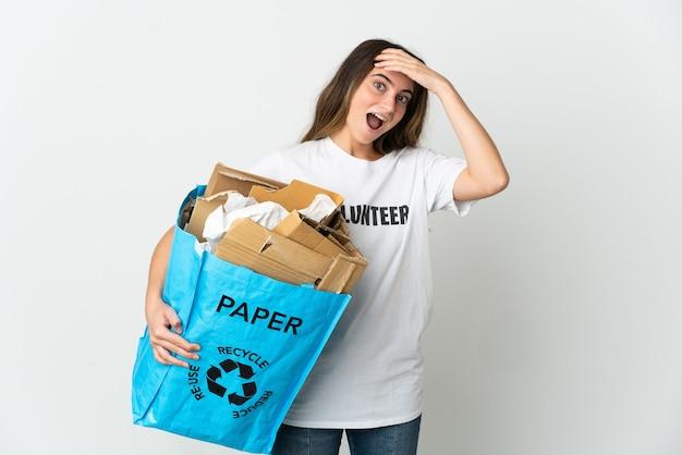 Giovane donna che tiene un sacchetto di riciclaggio pieno di carta da riciclare isolato su bianco con espressione di sorpresa