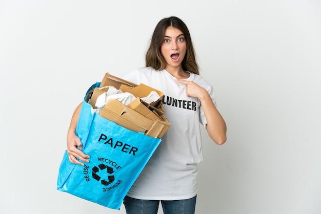Giovane donna che tiene un sacchetto di riciclaggio pieno di carta da riciclare isolato su bianco con espressione facciale di sorpresa