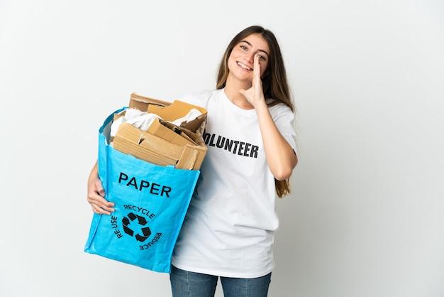 Giovane donna che tiene un sacchetto di riciclaggio pieno di carta da riciclare isolato