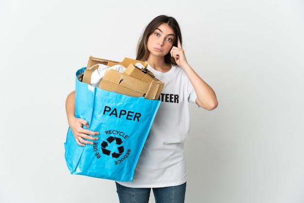 Giovane donna che tiene un sacchetto di riciclaggio pieno di carta da riciclare sul pensiero bianco un'idea