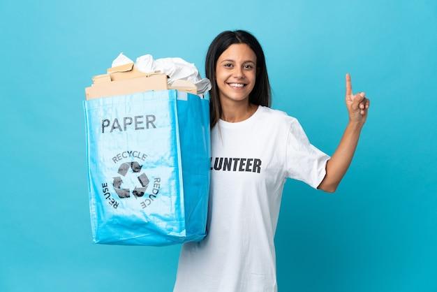 Giovane donna che tiene un sacchetto di riciclaggio pieno di carta che mostra e che solleva un dito in segno del meglio