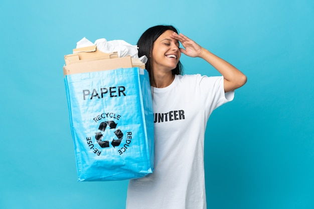 Giovane donna che tiene un sacchetto di riciclaggio pieno di carta che sorride molto