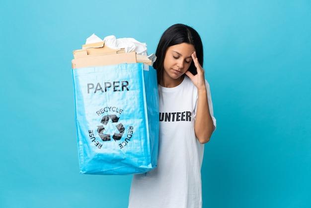 Giovane donna che tiene un sacchetto di riciclaggio pieno di carta con l'emicrania
