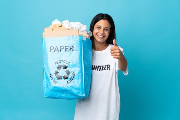 Giovane donna che tiene un sacchetto di riciclaggio pieno di carta con i pollici in su perché è successo qualcosa di buono