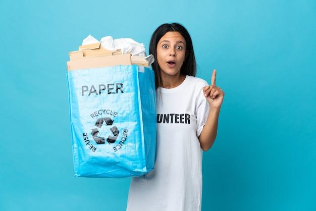 Giovane donna che tiene un sacchetto di riciclaggio pieno di carta