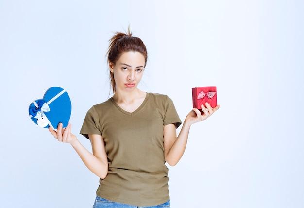 Giovane donna che tiene in mano scatole regalo a forma di cuore rosso e blu e sembra confusa a causa della scelta